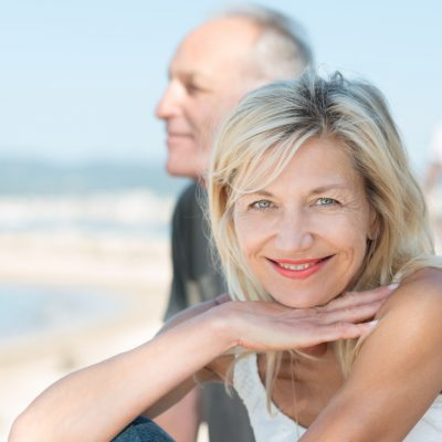 Smiling tanned mature woman at the beach with her husband turning to smile at the camera as they enjoy a healthy active lifestyle