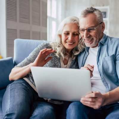 Love lives forever! Senior couple at home. Handsome old man and attractive old woman are spending time together. Sitting on a sofa with laptop.
